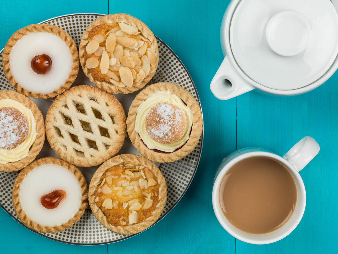 Plate of Assorted Individual Cakes or Tarts With a Pot of Tea