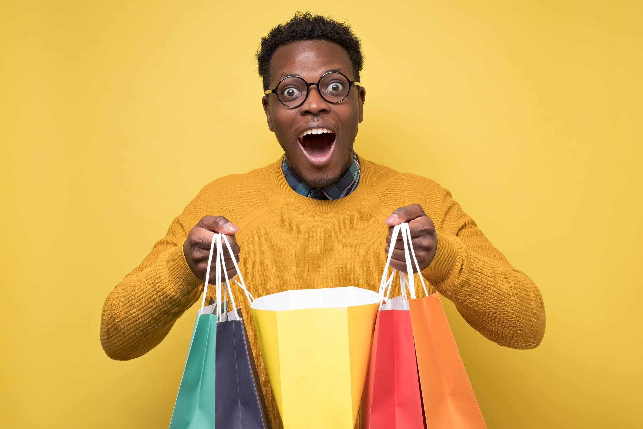 Handsome african american young man holds shopping paper bags