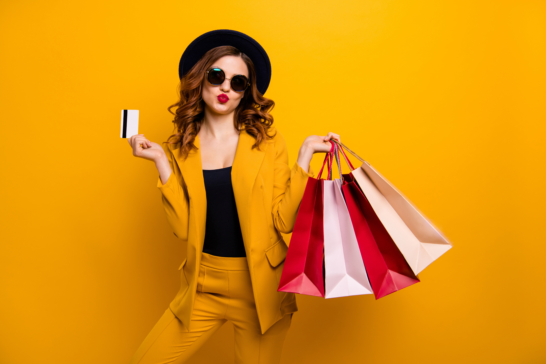 beautiful girl holding a debit card and shopping bags